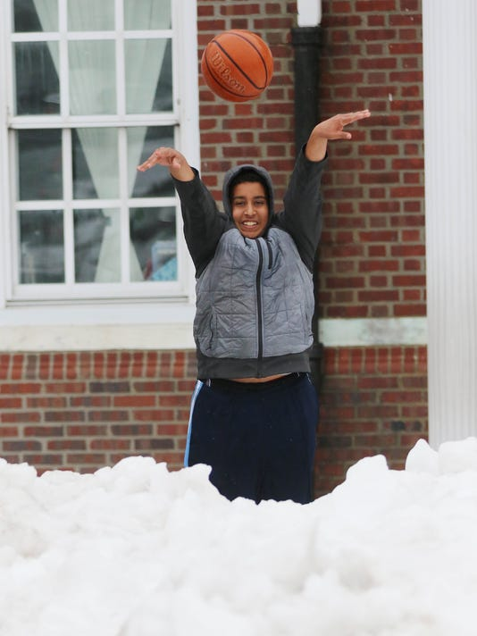 Rafat Saada 15 of Clifton comes out in the cold to shoot baskets on the asphalt basketball court that was partially cleared of snow at Clifton Elementary School 1.