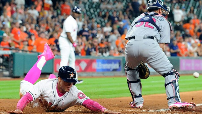 Houston Astros' George Springer, left, slides safely home past Seattle Mariners catcher Steve Clevenger on Carlos Correa's RBI-single in the seventh inning of a baseball game Sunday, May 8, 2016, in Houston. (AP Photo/Eric Christian Smith)