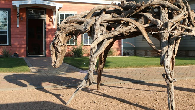 A sculpture of a horse crafted from driftwood is on display outside of Anthony Fuentez's studio in Old Town.