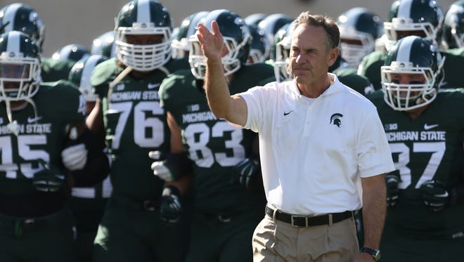 Michigan State head coach Mark Dantonio leads his players over to the student section before action against Michigan on Saturday, Oct. 25, 2014, at Spartan Stadium in East Lansing, Mich.