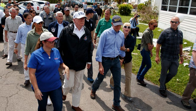 President Donald Trump, first lady Melania Trump, second row left, and Vice President Mike Pence tour Naples Estates, a neighborhood affected by Hurricane Irma, Thursday, Sept. 14, 2017, in Naples, Fla.