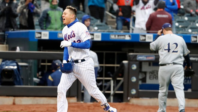 New York Mets' Wilmer Flores, left, runs the bases after hitting a ninth-inning walkoff solo home run as Milwaukee Brewers relief pitcher Matt Albers heads to the dugout after allowing the hit during a baseball game, Sunday, April 15, 2018, in New York.