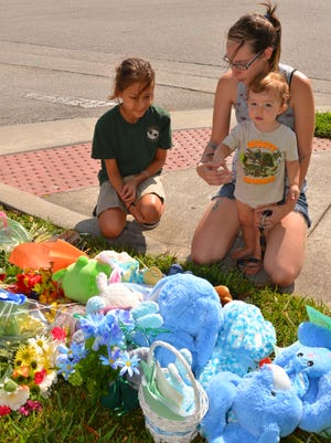 Jennifer Humphrey, holding her son Benjamin Carmel, brought her niece Kayla Heck to the site of the accident so she could leave a note and a teddy bear. She attended school with the boy who was killed. Every few minutes a car would stop and a parent with children, friend or acquaintance would add something to the roadside memorial for the young boy killed on his bike riding home from school Wednesday on Eldron Blvd. in Bayside Lakes.