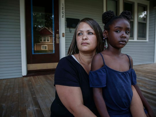 Jodi Bruce sits with her granddaughter, Zi'leyah Bennett, 5, on the front porch of the home she owns in Des Moines. Her home is located in an area that is being proposed for an expansion of the River Bend local historical district. Bruce strongly opposes the expansion and fears it could mean forcing low-income families to pay high costs to keep their homes to code or move out.