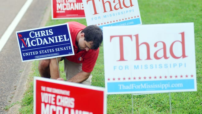 Alec Jones straightens a Chris McDaniel signs outside the voting booths at the Oxford Conference Center in Oxford, Miss., Tuesday, June 24, 2014. Voters go to the polls Tuesday to vote in the Republican primary runoff election between incumbent Sen. Thad Cochran and McDaniel. The winner will face Democrat Travis Childers in November's general election. (AP Photo/Oxford Eagle, Bruce Newman) MAGS OUT, NO SALES, MANDATORY CREDIT ORG XMIT: MSOXF201
