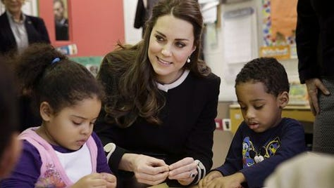 Kate, the Duchess of Cambridge, sits next to 4-year-olds April, left, and Sammy in a pre-school class at the Northside Center for Childhood Development today  in New York. Kate and Prince William arrived in New York City on Sunday, their first official visit to the U.S. since a 2011 trip to California and their first taste of the Big Apple.