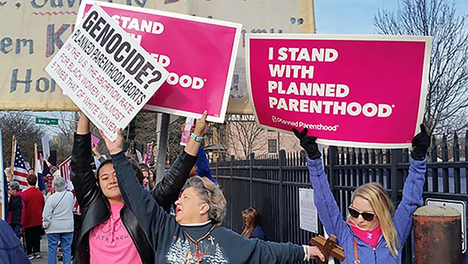 A Planned Parenthood supporter and opponent try to block each other's signs during a Feb. 11 protest and counterprotest in St. Louis.