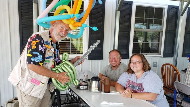 Diners at The Station in Kewanee were entertained Sunday by Doug Smith, a balloon artist with The Unique Twist & Twisting Crew. Shown, long time patrons, Lyndon and Kimberly Hartz from Wyoming, enjoyed the entertainment. Smith performed at the restaurant from 8 a.m. to noon. On Friday, The Station opened its dining room to inside diners, although many diners still preferred to dine outside.