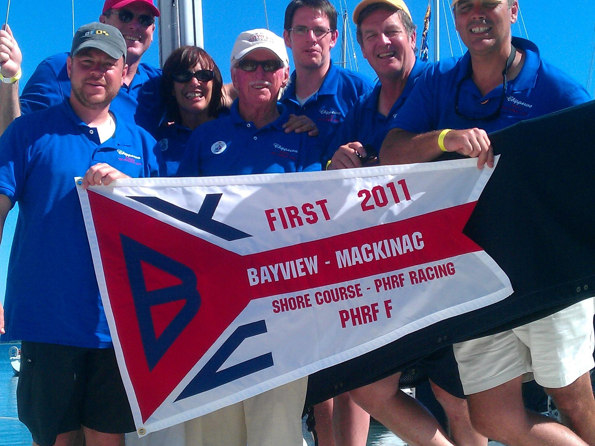 The crew of Chippewa holds their pennant for first place in their class. From left to right are Trevor Floyd, Don Robinson, Pam Wall, Bob Wall, Rob Wall, Greg Cyrul and Chris Cyrul.
