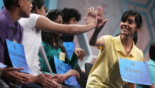 Eesha Sohail (R) of Bakersfield, Calif., hi-fives another speller after she correctly spelled her word during round three of the 2014 Scripps National Spelling Bee competition on May 28 in National Harbor, Md.