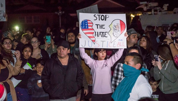 Protesters hold signs in front of an LAPD officer's