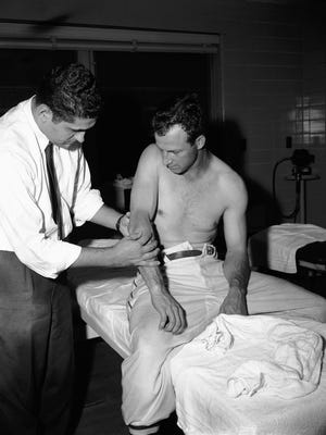 Dr. Stan London examines the arm of Cardinal outfielder Stan Musial after he was struck by a pitched ball in fifth inning of game between the Cardinals and Philadelphia at Busch Stadium in St. Louis, Missouri, Sept. 9, 1955. Examination revealed that it was only slightly injured and no bone was fractured.