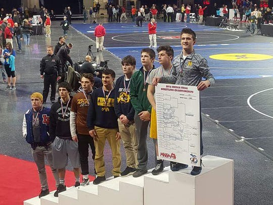 Hartand's Reece Hughes stands atop the podium after