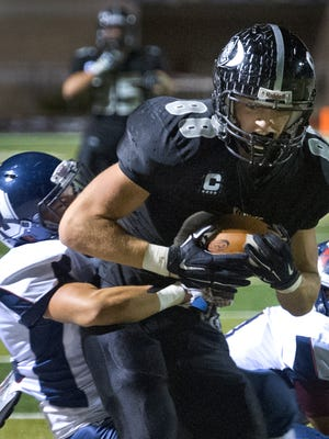 Oñate High's James Martin tries to break a tackle by Deming defender Cristian Sanchez during second quarter action Friday night at the Field of Dreams.