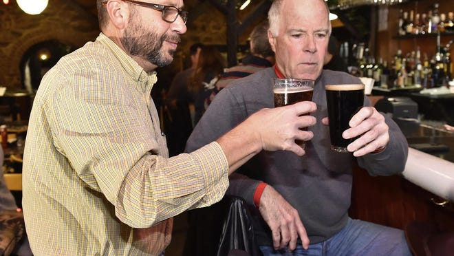 """In this Dec. 6, 2016 photo, Terry Ditzler, left, and Garry Bertrand, right, toast their 100th visit together to bars throughout Lancaster County, Pa. at Bube's Brewery in Mount Joy, Pa. Ditzler and Bertrand created a """"Retired Guys Beer Afternoon"""" website to chronicle their effort to visit every beer-selling, nonsmoking bar in Lancaster County, trying a new bar every other Tuesday afternoon. (Suzette Wenger/LNP via AP)"""