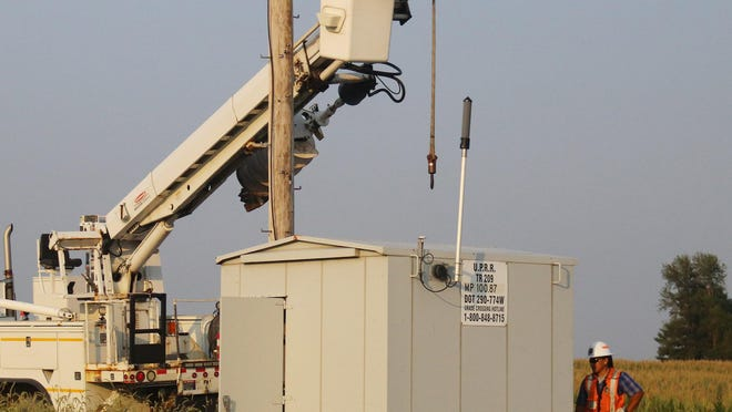 Union Pacific employees work on a pole next to a shed along the tracks between Pontiac and Chenoa.
