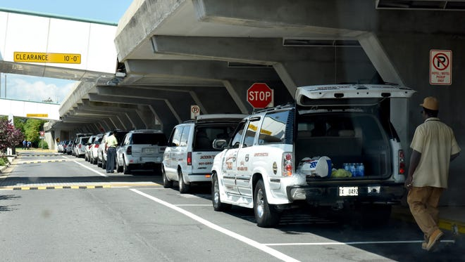 Taxis line up outside the Jackson Medgar Wiley Evers International Airport entrance earlier this year. The Jackson City Council is considering a proposal that would make Uber adhere to the same regulations as taxi services.