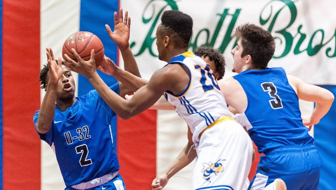 Milton's Tre Sherwood (20) and U-32's Jordan Hawkins (2) go for a loose ball during Saturday's Division II high school boys basketball semifinals vs. U-32 at Barre Auditorium.
