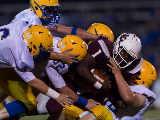 Henderson County's Skip Peterson (1) is taken down by a sea of Caldwell County Tiger defensemen in the first quarter at Henderson County High School in Henderson, Ky., on Friday, Sept. 15, 2017.