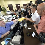 Rowan County deputy clerk Brian Mason, left, hands James Yates and William Smith Jr. their marriage license at the Rowan County Judicial Center in Morehead, Ky., on Friday. Yates and Smith had tried several times to obtain the document but had been denied.