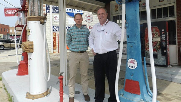 Charles Smith, right, stands with his son at the filling station in this 2013 file photo.