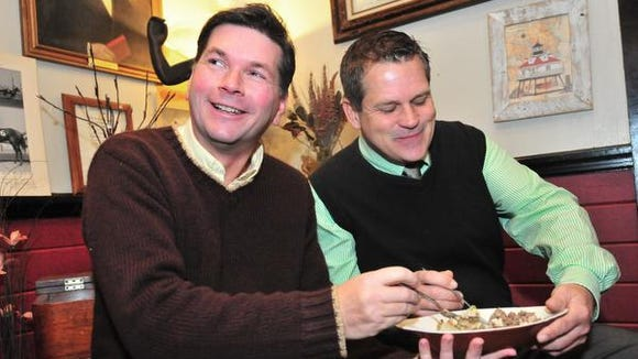 Dale Slotter (left) and John Buchheit, his partner of 22 years, Dale share a shepherds pie  last year at their restaurant, Crabby Dicks, in Delaware City.