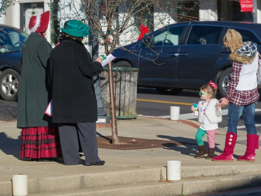Kenli Caldwell, 2, taps her foot as she holds her mother's hand, Alison Caldwell, and lessons to caroling on the corner of State and Jennings last year.
