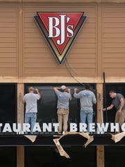 Construction workers install glass at BJ's Restaurant & Brewhouse.