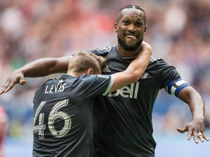 Vancouver Whitecaps' Kendall Waston, back, and Brett Levis celebrate Waston's second goal against the New York Red Bulls during the second half of an MLS soccer game Saturday, Aug. 18, 2018 in Vancouver, British Columbia. (Darryl Dyck/The Canadian Press via AP)