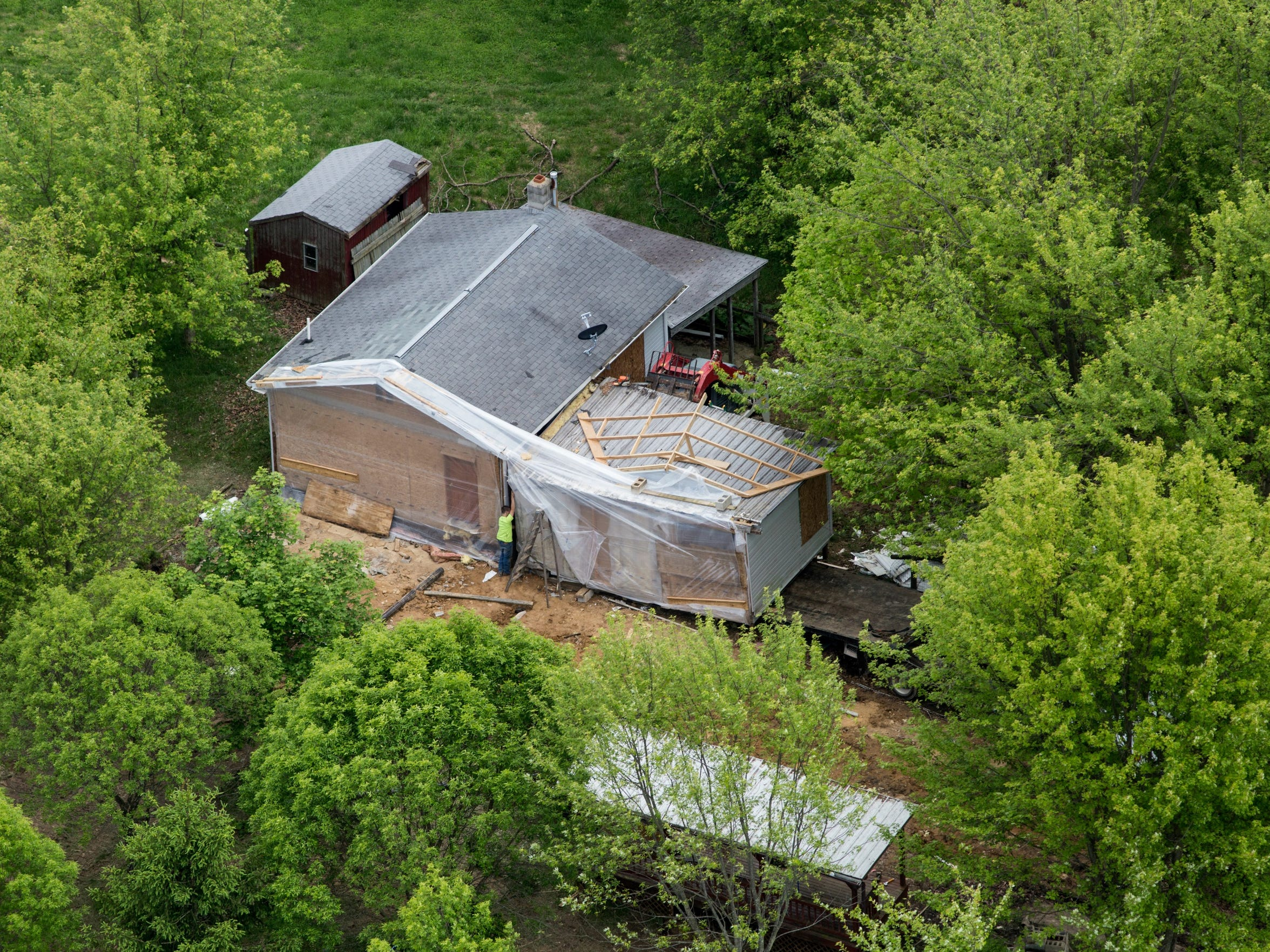 May 13, 2016: A man pictured below finishes securing the addition that was built onto the trailer in which Dana Rhoden and two of her children were killed April 22.
