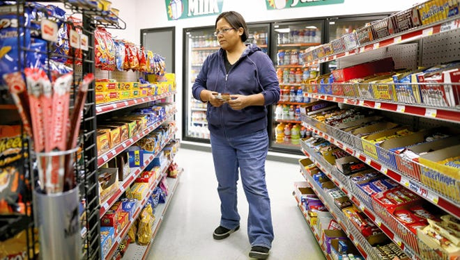 Cashier Vanessa Rodriguez stocks the shelves Nov. 21, 2014, at the Quick Stop gas station and convenience store in Shiprock.