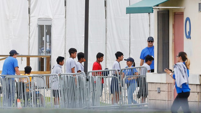 "Immigrant children walk in a line outside the Homestead Temporary Shelter for Unaccompanied Children a former Job Corps site that now houses them, on Wednesday, June 20, 2018, in Homestead, Fla. U.S. Rep. Carlos Curbelo said he found it ""troubling"" to see two of his Democratic colleagues turned away from the Miami-area detention center for migrant children. (AP Photo/Brynn Anderson)"