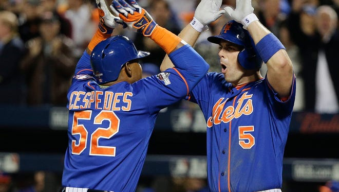 New York Mets' David Wright (5) greets Yoenis Cespedes (52) after Cespedes hit a two-run home run against the Los Angeles Dodgers during the fourth inning of baseball's Game 3 of the National League Division Series, Monday, Oct. 12, 2015, in New York.