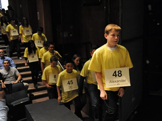 Spelling champions file onstage for the first rounds of the spelling bee.