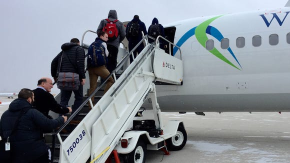 Butler's travel party boards a jetliner for a charter flight to Newark, N.J.
