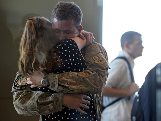 Captain Rob Willoughby hugs his wife, Laura, at the