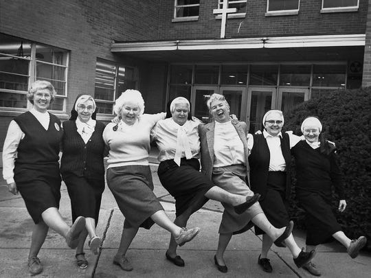 Sister Mary Edwina Butler, far right in photo, and Sister Mary Walter Hickey, third from right, along with other nuns, are caught in a moment of celebration in 1990 outside Notre Dame High School in Elmira.