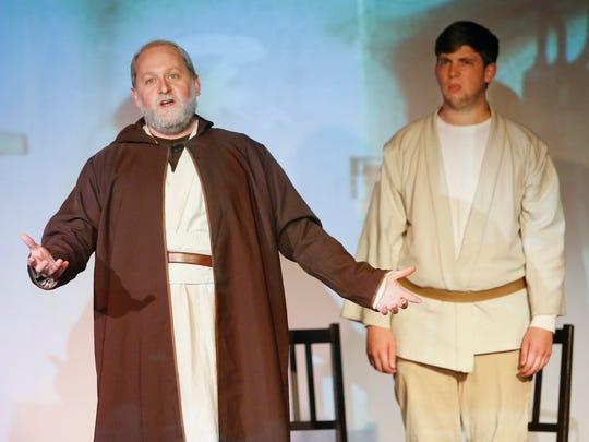 """Obi-Wan Kenobi (Shaun Yates) sings as Luke Skywalker (Caleb Duffy) shares the stage during a rehearsal for the Bootless Stageworks production of """"Star Wars: A New Musical Hope."""""""