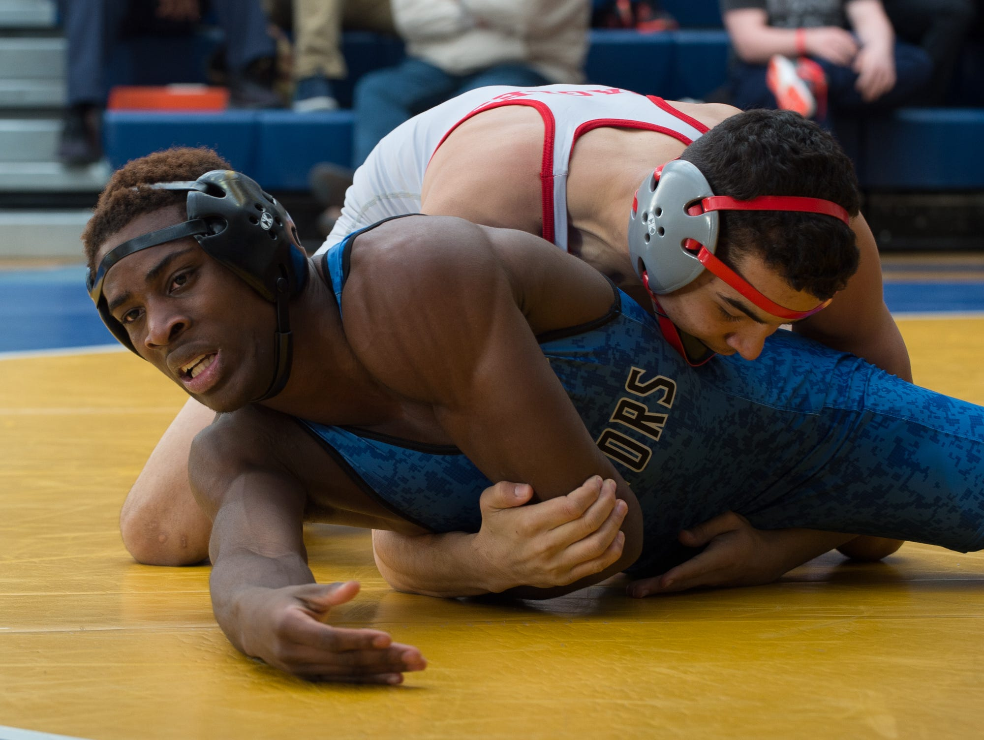 Smyrna's Nate Bryant (top) and Dover's Divine Watkins wrestle in the 152 pound championship match at the Henlopen Conference wrestling tournament at Sussex Central High School.