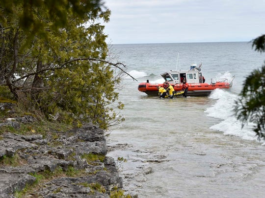 A kayaker is transported from a U.S. Coast Guard boat to a stretcher along the Lake Michigan shoreline Friday. Two men kayaking off Cave Point County Park died Friday after their vessels capsized.