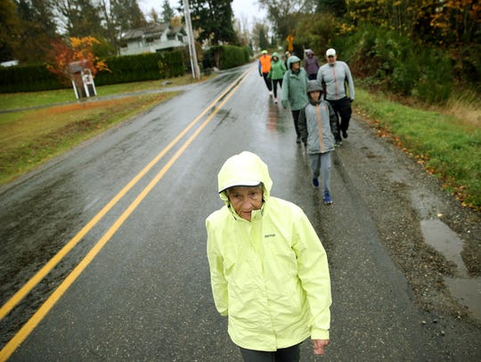 Juanita Adkins, center, leads her family on a training walk in her Olalla neighborhood. Adkins, 92, will attempt her 12th half-marathon on Sunday in Seattle.
