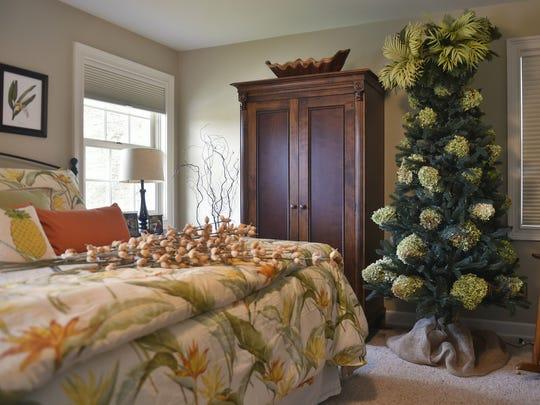 A tropical Christmas tree enhances the Hawaiian theme inside the master bedroom of Jeff and Nancy Warner of Liberty Grove.