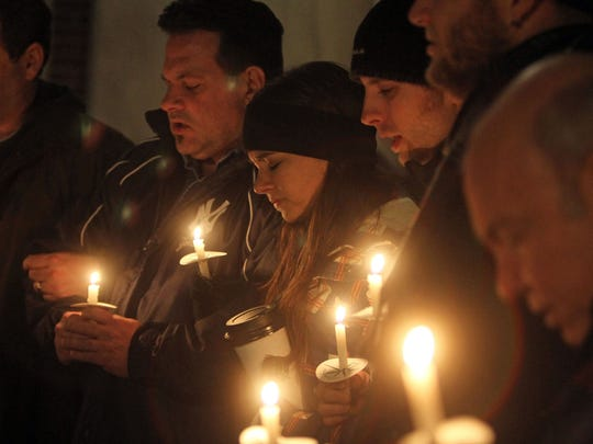 Members of Connections Church in Newtown, Connecticut, take part in a candlelight vigil outside the old town hall in Newtown on Dec. 15, 2012, a day after the mass shooting at Sandy Hook Elementary School.