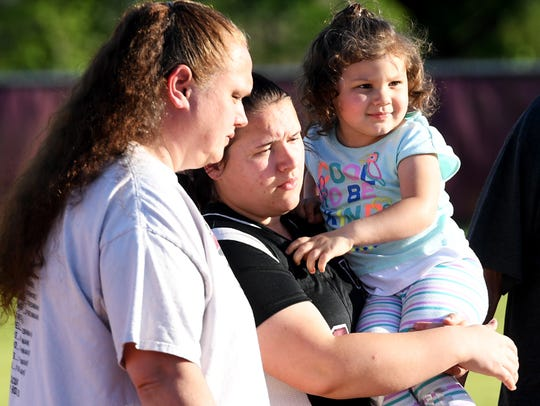 Ashley Barlow holds her 3-year-old daughter, Madalyn Cook, as she prepares to be recognized on senior night at West Carroll High School. At left is Ashley's mother, Brenda.