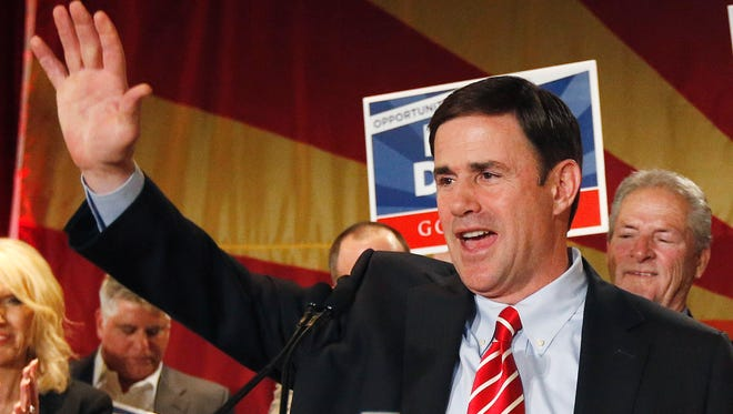 In this Nov. 4, 2014, file photo, Doug Ducey, who was elected as Arizona governor, waves to supporters on Election Night in Phoenix. Republicans swept every statewide office in November's general election, retaining their control over the governor's office, secretary of state, treasurer, attorney general and schools superintendent.