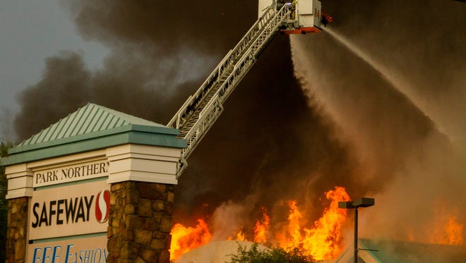 Firefighters attempt to put out flames on July 11, 2018, after a Safeway grocery store caught fire on the corner of North 35th Avenue and West Northern Avenue in Phoenix, Arizona.
