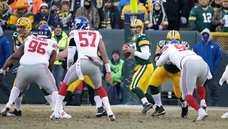 Green Bay Packers quarterback Aaron Rodgers (12) looks downfield from behind his wall of blockers against the New York Giants at Lambeau Field Sunday, January 8, 2017.