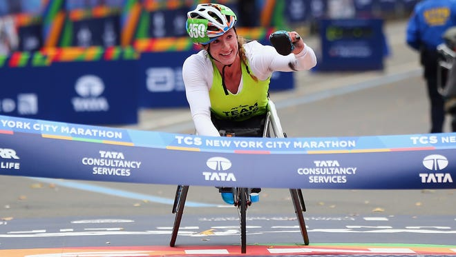 Tatyana McFadden of the United States celebrates as she crosses the finish line to win the women's professional wheelchair division during the 2015 TCS New York City Marathon.