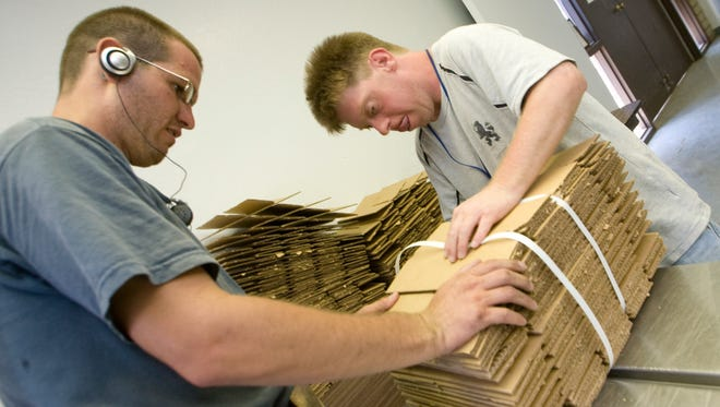 Marc Center clients Ronnie Burris (left) and Shawn Cecchet bundle cardboard dividers for boxes in the Freestone Rehabilitation Center in this 2008 file photo.