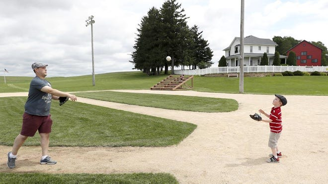 Jeremiah Bronson, of Ames, Iowa, plays catch with his son Ben (right) June 5 on the field at the Field of Dreams movie site in Dyersville, Iowa.